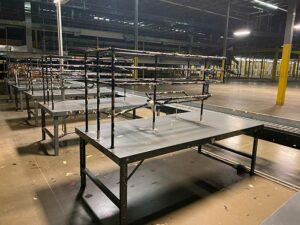 Used Packing Tables in a row with racks